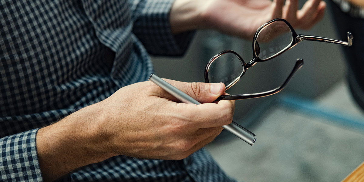 A man holding eye glasses and a pen