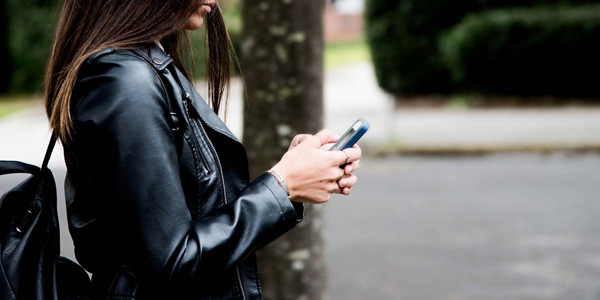 A woman using her phone while walking down the street.